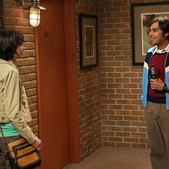 Raj talking to Lucy outside his apartment - Note beer bottle.