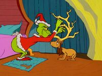 Grinch ties antlers on Max's head