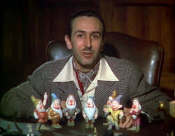 A color photograph of a man sitting behind a desk. Seven figurines are standing before him.