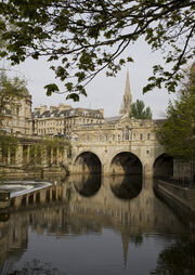 Yellow/Gray stone bridge with three arches over water which reflects the bridge and the church spire behind. A weir is on the left with other yellow stone buildings behind.