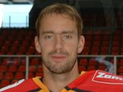 An ice hockey players face and shoulders. He has short blrown hair and is not wearing a helmet.