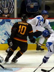 An ice hockey player dressed in a black and orange jersey watchfully skates in front of an opposing player who is playing the puck.