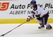 An ice hockey player in his late teens in mid-stride, carrying the puck. He is looking down towards the puck on his outstretched stick.