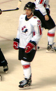 Hockey player in white Canada uniform. He stands on the ice and looks away from the camera.