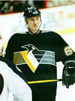 Upper body of a man wearing a black uniform with a stylized penguin in yellow, grey and white on the chest. He is looking into the distance.