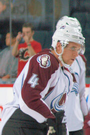An ice hockey player stands facing the right of the camera. He is wearing a white helmet and a burgandy and white uniform with a large burgandy A on his chest.