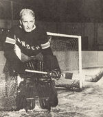 The mask-less ice hockey goalie stands in the crease wearing the small leg pads and gloves of yesteryear.