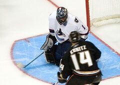 An ice hockey goaltender wearing a white jersey on his knees to make a save. He is looking downwards to the right as an opposing player in black skates towards him.
