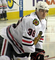 Hockey player in white uniform with a picture of crossed hockey sticks on the shoulder and the painted face of an indigenous person on the chest. He is crouched on the ice, feet further than shoulder width apart.