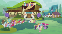 Ponies gathered outside the bowling alley S5E9