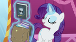 Rarity levitates one of the books from the bag S5E22