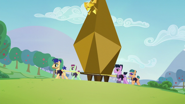 File:Backup dancers lifting a giant bronze capsule S5E24.png