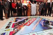 Lagos state governor, Babatunde Raji Fasholarolls (centre), rolls a dice during the presentation of the Lagos-themed Monopoly board game