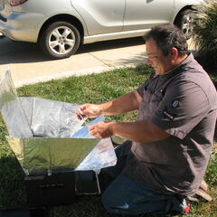 Rick adjusts the reflectors on his box-style solar cooker, made from an old toaster oven.