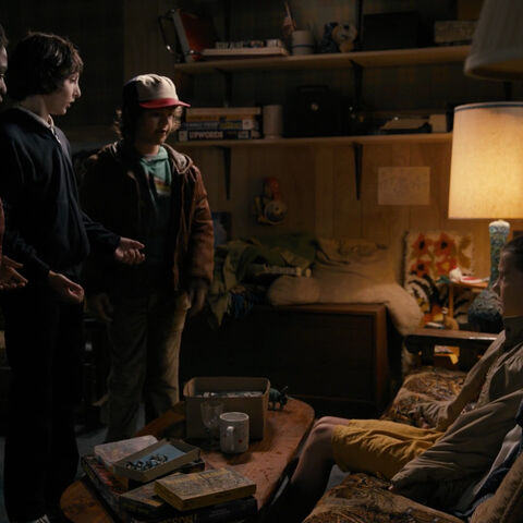 The boys question Eleven in Mike's basement.