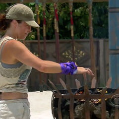Laura burning the Hidden Immunity Idol clue.