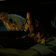 Haigh zündet Parrish im Polizeiauto an.