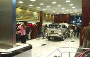 Car showroom with an SUV and customers, along with a metal waterfall fixture and paintings.