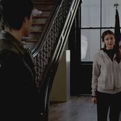 Elena and Damon talking next to the stairs