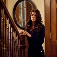 Elena looks to see what fell in the kitchen..