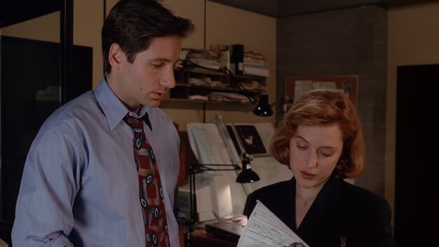 File:Fox Mulder shows Dana Scully paperwork.jpg
