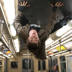 Peter Parker, sticking to the ceiling of a subway train interior.