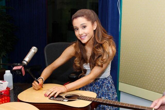 File:Ariana signing a guitar .jpg