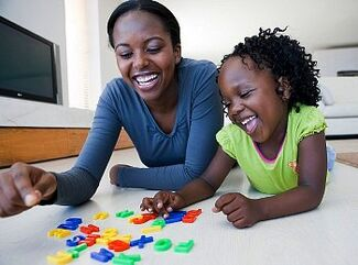 Woman and Child Playing with Letters from blackdoctor