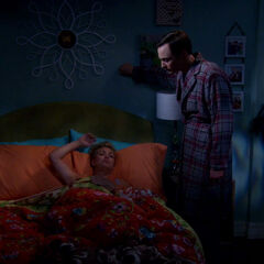 Sheldon waking up Penny in her bedroom.