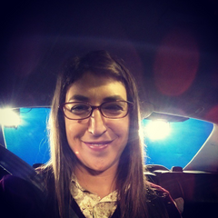 Mayim as Amy in a studio car in front of a blue screen.