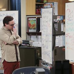 Leonard looks worried at what is on the whiteboards.