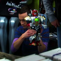 Sheldon playing with a robot at the comic book store.