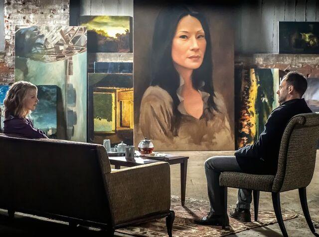 File:Natalie Dormer guest stars as Jamie Moriarty Irene Adler with Jonny Lee Miller as Sherlock Holmes with a painting of Joan Watson in CBS Elementary Season 2 Episode 12 The Diabolical Kind.jpg