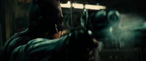 Batman fires a shot at a thug with his Grapple Gun