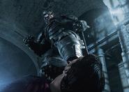A battered Batman stepping on Superman's throat