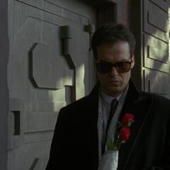Bruce leaves roses at the spot where his parents were murdered.