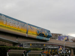 A monorail stamping a painted Light Cycle which leaves an orange trail behind. The second cart also has the Tron Legacy title.