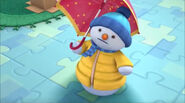 Chilly in his snowclothes with an umbrella