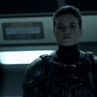 Diana Bentley as Sergeant Grimes aboard MCRN Donnager takes James Holden from his cell to interrogation by Lieutenant K. Lopez