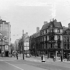 The aforementioned High Street crossroads, leading to East and West Street. All buildings, except for the conspicuously small and elephant-in-the-room nightclub, built in the space of the destroyed Blithebeth World War I monument, an incredibly tall tribute and testament to the true mortal coil (and toil) of World War I. Note the rations-infering billboard in the middle, which was still relevant at the time of this photo's creation, 1956. There is another open space for another bombed building in the central background, on East Street.