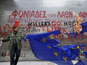 File:Greece-man-burning-flag-in-front-of-graffiti.jpg