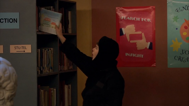 File:Season 1, Episode 2 - Wendell sneaking book on shelf.png