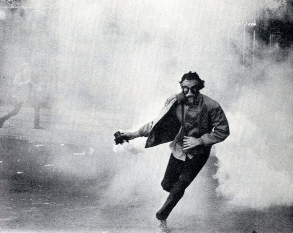File:Vietnam War Protester Wearing An M9A1 Gas Mask Hurls A Tear Gas Canister Back At Police.jpg