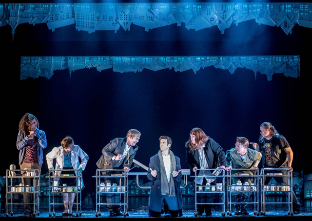 File:Andy Karl as Phil Connors alongside characters holding trolleys.png