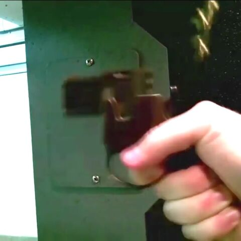 The pistol deflecting a spent casing off its hammer.