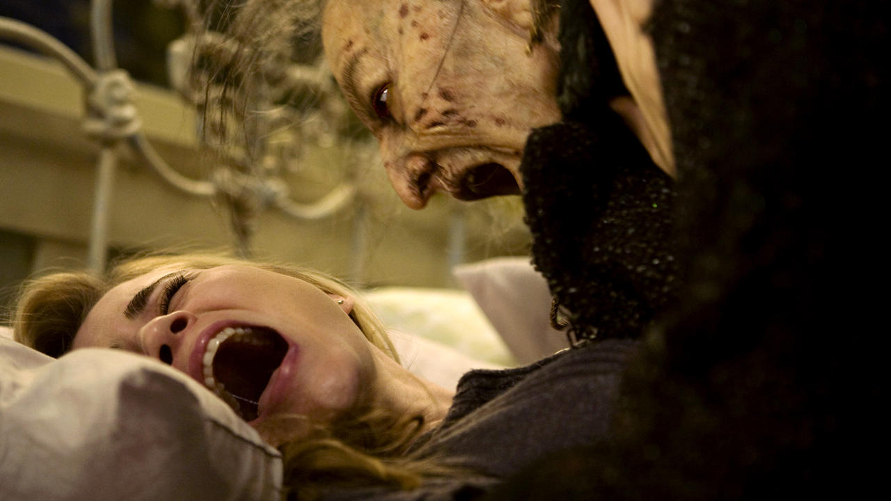 Still from Drag Me to Hell. A young blonde woman screams as she is pinned down on a bed by a terrifying old witch with sunken skin and wispy grey hair, who shrieks in her face.