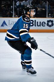 Hockey player in blue and black uniform. He extends his stick to his right, and faces to the right of the camera.