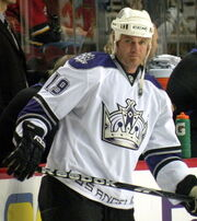 Hockey player in white uniform with a large crown in the middle. He holds a stick horizontally