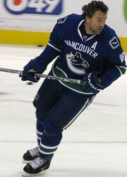 Hockey player in dark blue Vancouver uniform. He leans forward, holding his stick aloft.