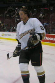 "A brown haired hockey player in a white and black uniform with the wordmark ""Ducks"" across his chest skates as he looks into the distance."